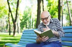 Homme plus âgé dans la lecture occasionnelle dehors Image stock