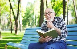 Homme plus âgé dans la lecture occasionnelle dehors Photos stock