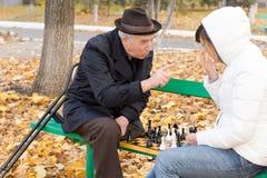 Homme plus âgé discutant pendant une partie d'échecs Photo libre de droits