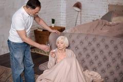 Homme plus âgé donnant le verre d'eau à son épouse malade Photographie stock libre de droits