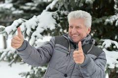 Homme plus âgé en hiver avec des pouces  Photographie stock