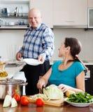 Homme plus âgé et femme mûre faisant les travaux domestiques ensemble Photographie stock libre de droits