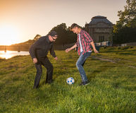 Homme plus âgé et garçon jouant le football dans le domaine au coucher du soleil Photo libre de droits
