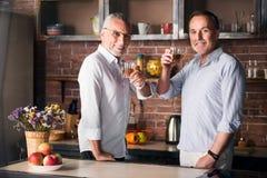 Homme plus âgé et son fils buvant dans la cuisine Photos stock