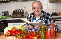 Homme plus âgé faisant cuire un repas sain image libre de droits
