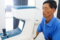 Homme plus âgé faisant examiner des yeux de hes par un ophtalmologiste sur un outil d'essai dans la clinique moderne photo stock