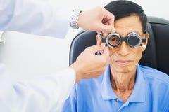 Homme plus âgé faisant examiner des yeux de hes par un ophtalmologiste sur un outil d'essai dans la clinique moderne photo libre de droits