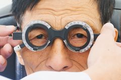 Homme plus âgé faisant examiner des yeux de hes par un ophtalmologiste sur un outil d'essai dans la clinique moderne, image stock