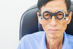 Homme plus âgé faisant examiner des yeux de hes par un ophtalmologiste sur un outil d'essai dans la clinique moderne, photographie stock libre de droits