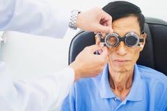Homme plus âgé faisant examiner des yeux de hes par un ophtalmologiste sur un outil d'essai dans la clinique moderne, photo libre de droits