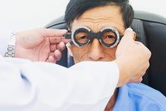 Homme plus âgé faisant examiner des yeux de hes par un ophtalmologiste sur un outil d'essai dans la clinique moderne images libres de droits