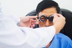 Homme plus âgé faisant examiner des yeux de hes par un ophtalmologiste sur un outil d'essai dans la clinique moderne photos stock