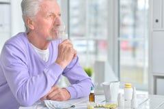 Homme plus âgé faisant l'inhalation Photos stock