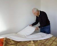 Homme plus âgé faisant son lit. Image libre de droits