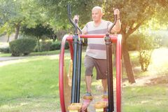 Homme plus âgé heureux établissant sur l'équipement public de sports dans le gymnase extérieur Homme folâtre faisant l'exercice p image stock