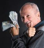 Homme plus âgé heureux montrant des dollars Photos libres de droits