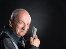 Homme plus âgé heureux montrant des dollars Photo libre de droits