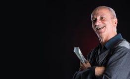 Homme plus âgé heureux montrant des dollars Photographie stock