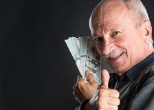 Homme plus âgé heureux montrant des dollars Images stock