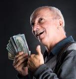 Homme plus âgé heureux montrant des dollars Image libre de droits