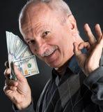 Homme plus âgé heureux montrant des dollars Images libres de droits