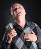 Homme plus âgé heureux montrant des dollars Photo stock