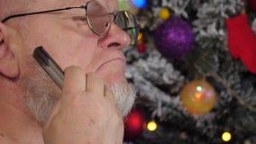 Homme plus âgé heureux peignant sa barbe grise avec le peigne sur le fond de l'arbre de Noël dans des guirlandes, boules vertes d banque de vidéos
