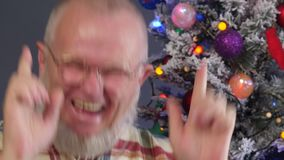 Homme plus âgé heureux peignant sa barbe grise avec le peigne sur le fond de l'arbre de Noël dans des guirlandes, boules vertes d clips vidéos