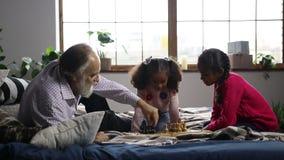 Homme plus âgé jouant des échecs avec la petite-fille mignonne banque de vidéos