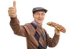 Homme plus âgé joyeux ayant le sandwich et faisant le pouce vers le haut du signe images stock
