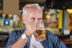 Homme plus âgé joyeux se reposant aux week-ends photographie stock