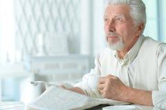 Homme plus âgé lisant un journal Image stock