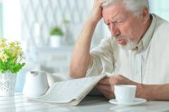 Homme plus âgé lisant un journal Images stock