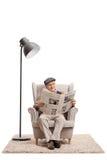 Homme plus âgé lisant un journal dans un fauteuil Photographie stock libre de droits