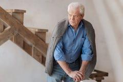 Homme plus âgé malheureux se tenant dans la chambre Photos libres de droits