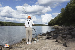 Homme plus âgé marchant suivant la ligne de rivage avec le marcheur et une canne à pêche au-dessus de son épaule Photographie stock