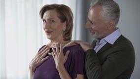 Homme plus âgé mettant le collier de perle sur l'épouse et l'embrassant, célébration, actuelle clips vidéos