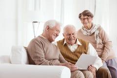 Homme plus âgé montrant l'ordinateur portable Image stock