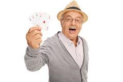 Homme plus âgé montrant quatre as Photos libres de droits