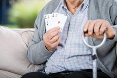 Homme plus âgé montrant quatre as tout en se reposant Photos stock