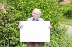 Homme plus âgé montrant un tableau blanc vide Photo stock