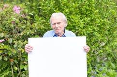 Homme plus âgé montrant un tableau blanc vide Images stock
