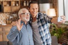 Homme plus âgé ondulant à l'appareil-photo tout en prenant des selifes avec le fils Images libres de droits