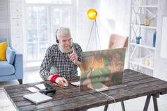 Homme plus âgé optimiste causant avec des amis tout en jouant le jeu Photo libre de droits