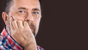 Homme plus âgé réfléchi avec la main près du visage Photographie stock