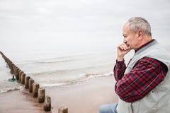 Homme plus âgé réfléchi se tenant sur la plage Images libres de droits