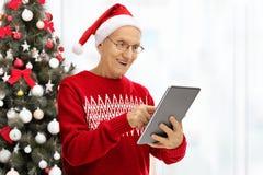 Homme plus âgé regardant le comprimé devant l'arbre de Noël Photo libre de droits