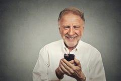 Homme plus âgé regardant son téléphone intelligent tandis que la messagerie textuelle images stock