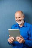 Homme plus âgé riant de l'information sur son comprimé Image stock