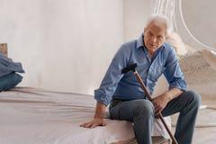 Homme plus âgé sérieux seul s'asseyant dans la chambre Photo libre de droits